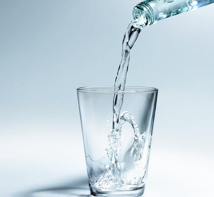 Bottled water being poured into glass, close-up